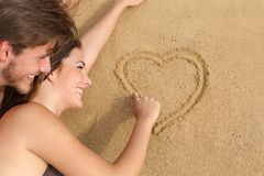 Couple in love drawing a heart on the sand of the beach royalty free stock images