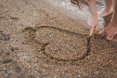 Couple in love drawing a heart on the sand. Lovers heart draw in the sand, romance, concept, recreation Royalty Free Stock Images