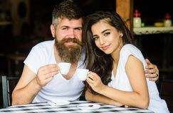 Couple in love drink black espresso coffee in cafe. Man with beard and attractive happy smiling girl hugs and drinking. Coffee. Pleasant family moment. Enjoy Stock Photos