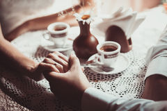 Couple in love drink coffee in cafe, holding each other's hand. Photo is processed in coffee color tone. Concept of male and female hands, love and coffee Stock Images