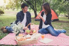 Couple in love drink a orange juice and fruits on summer picnic, leisure, holidays, eating, people and relaxation concept stock image