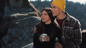 Couple in love drink tea from a mug of thermos on the background of mountains. Tourists sitting on stones and looking on stock video