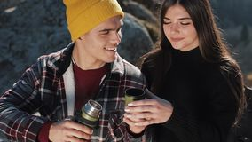 Couple in love drink tea from a mug of thermos on the background of mountains. Tourists sitting on stones and looking on stock video footage