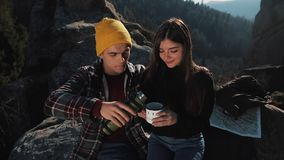 Couple in love drink tea from a mug of thermos on the background of mountains. Tourists sitting on stones and looking on stock footage