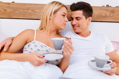 Couple in love drinking morning coffee in bed Royalty Free Stock Photo