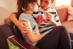 Couple in love drinking smoothie chilling on sofa in living room. Man and woman hugging enjoying drinks royalty free stock image