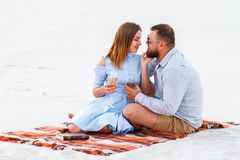 Couple in love drinking wine during romantic dinner on the beach, young couple kissing and holding glasses in hands Royalty Free Stock Photo