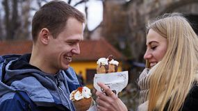 Couple in love eat Trdelnik in Prague royalty free stock photos