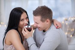 Couple in love eating sweet cake. Cute young couple in love eating sweet cake royalty free stock images