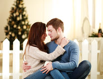 Couple in love embrace each other at home on festive decorations Royalty Free Stock Photography