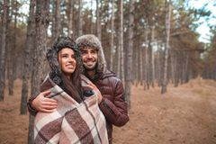 A couple in love embrace and look into the distance. Outdoors. Young couple in love embrace and look into the distance while in the autumn forest. Outdoors Stock Images