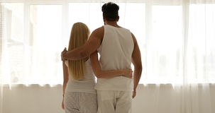 Couple love embrace walking to window open curtains mix race man woman rear view hug morning bedroom stock video