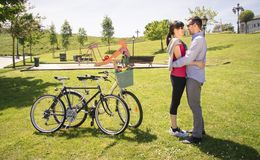 Couple in love embraced beside of bicycles on park Stock Photos