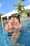 Couple in love embracing in private swimming pool. In love couple embracing in swimming-pool Stock Photography