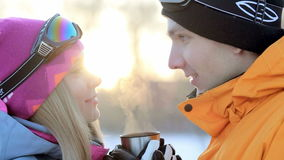 Couple in love is enjoying a drink in the backlit sunlight, man and woman drinking tea, coffee cup in the winter forest. Warming drink in the cup for a thermos stock video