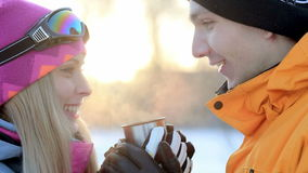Couple in love is enjoying a drink in the backlit sunlight, man and woman drinking tea, coffee cup in the winter forest. Warming drink in the cup for a thermos stock video footage