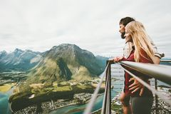 Couple in love enjoying mountains view traveling together. Lifestyle adventure vacations in Norway Rampestreken viewpoint stock photo