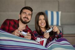 Couple in love enjoying their free time, sitting on a couch next to the window, playing video games and having fun. Couple in love enjoying their free time royalty free stock photography