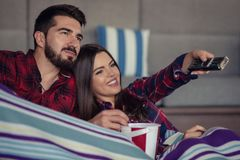 Couple in love enjoying their free time, sitting on a couch next to the window, playing video games and having fun. Couple in love enjoying their free time royalty free stock image