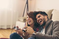 Couple playing games. Couple in love enjoying their free time, sitting on the living room floor, playing video games and having fun. Focus on the man stock photos