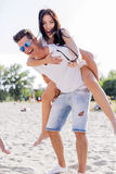 Couple in love enjoying their summer vacation as the man carries Royalty Free Stock Photo