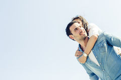 Couple in love enjoying their summer vacation as the man carries Royalty Free Stock Photography