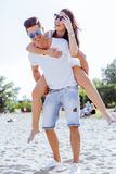 Couple in love enjoying their summer vacation as the man carries Stock Images