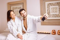 Couple in love enjoying wellness weekend and taking selfies in spa. Salon royalty free stock photo