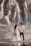 Couple in love in fabulous mountains hugging, Martian landscape. Lovers walk in the mountains in the summer. The girl in long light summer dress with a bouquet Royalty Free Stock Photo