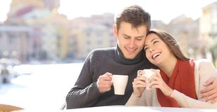 Couple in love flirting in a coffee shop. In a coast town street royalty free stock photos