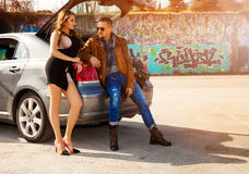 Couple in love flirting sitting at car trunk Stock Images