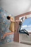 Couple in love, flying. Young couple jumping together inside a flat royalty free stock photos