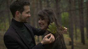 A couple in love in the forest at dawn. Young man hugging his girlfriend and played with her hair. He was carrying a. Green leaf from a tree. they are in the stock video footage