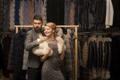 Couple in love among fur coat, luxury. Date, couple, love, men and woman. Woman in fur coat with man, shopping, seller and customer. Fashion and beauty, winter stock image