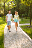 Couple in love goes on a park alley. Royalty Free Stock Photography