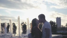 Couple in love guy and girl kissing near fountain on sunset background. HD, 1920x1080. Slow motion stock video footage
