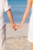 Couple in love hand in hand on beach in summer Royalty Free Stock Photo
