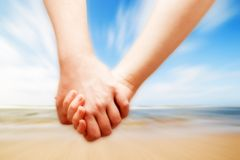 A couple in love hand in hand on the sunny beach Stock Photography