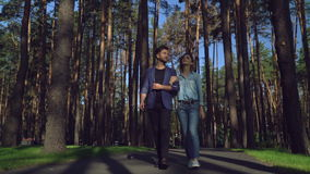 Couple in love with happiness smile . Young happy people on a romantic date in park with green grass on lawn and beautiful different trees. Caucasian girl and stock video