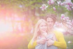 Couple in love. happy couple in love in spring magnolia. Flowers, smiling men and girl in garden with blossom tree outdoor on natural background royalty free stock images