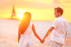 Couple in love happy at romantic beach sunset. Young interracial couple holding hands having romance and fun outside walking on beach during summer holidays Royalty Free Stock Photography