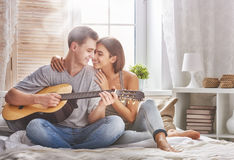 Couple in love. Happy couple in love. Stunning sensual portrait of young stylish fashion couple indoors. Young men playing guitar for his beloved girl stock images