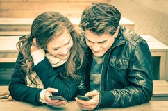 Couple in love having fun with modern phones Stock Photo