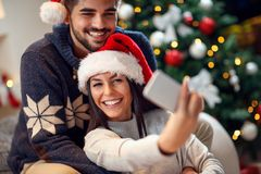 Couple in love having fun and take pictures of Christmas on mobi. Le phone at home royalty free stock images