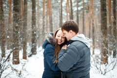 Couple in love having fun in winter forest. Couple in love having fun, winter forest at the background Royalty Free Stock Photo