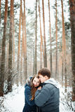 Couple in love having fun in winter forest. Young couple in love having fun, winter forest at the background, space for text Royalty Free Stock Photography