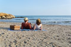 Couple in love having a picnic on a mediterranean beach at sunset stock photos