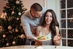Couple in love, having a romantic dinner. Christmas tree in the background royalty free stock photography
