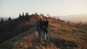 Couple in love hiking outdoors. Hikers man and woman trekking walking with backpacks in trail at sunset in mountains.  stock video