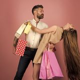 Couple in love hold shopping bag near pink wall. Girl and bearded men hold present pack, cyber Monday. Shopping and sale. Fashion shopaholic couple. Black royalty free stock photo